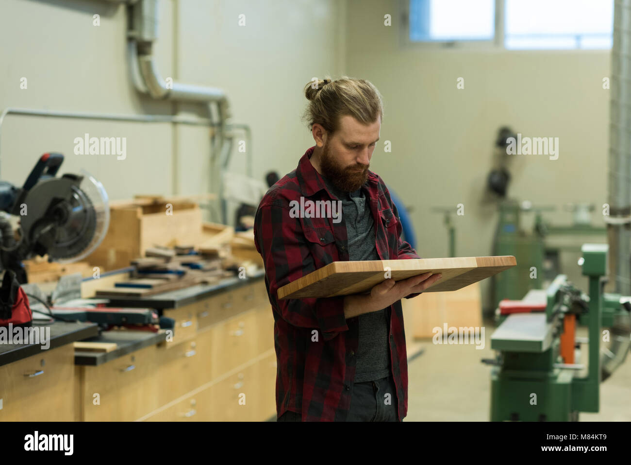 Male carpenter examining a wood furniture at workshop - Stock Image