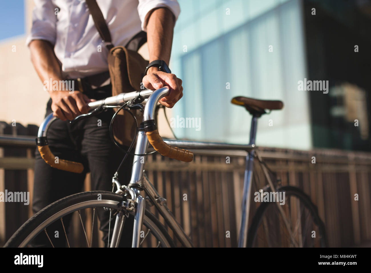 Businessman walking with his bicycle at office premises Stock Photo