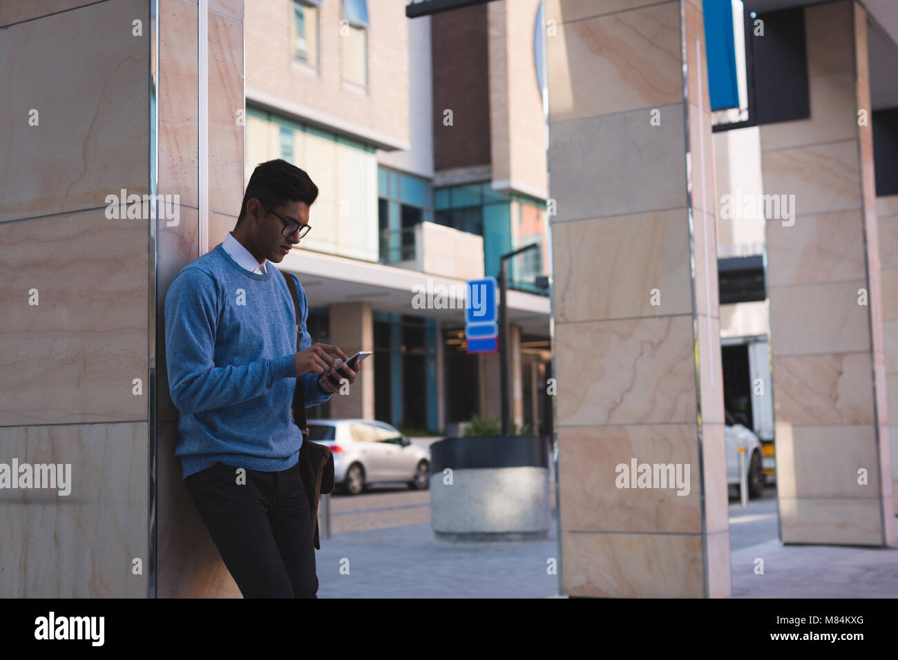 Businessman using mobile phone outside office premises - Stock Image