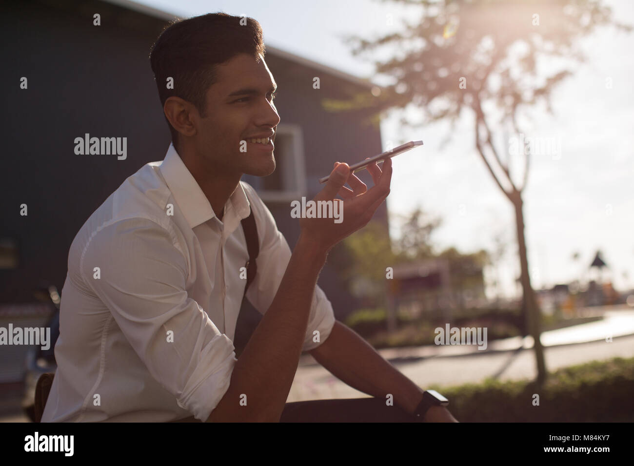Businessman talking on mobile phone in office premises - Stock Image