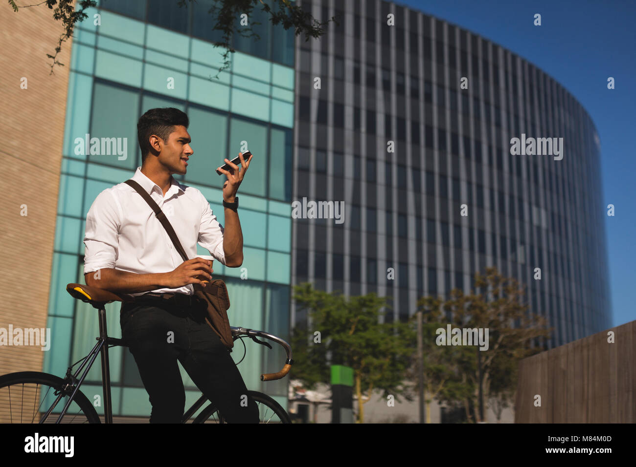 Businessman talking on mobile phone outside office premises - Stock Image