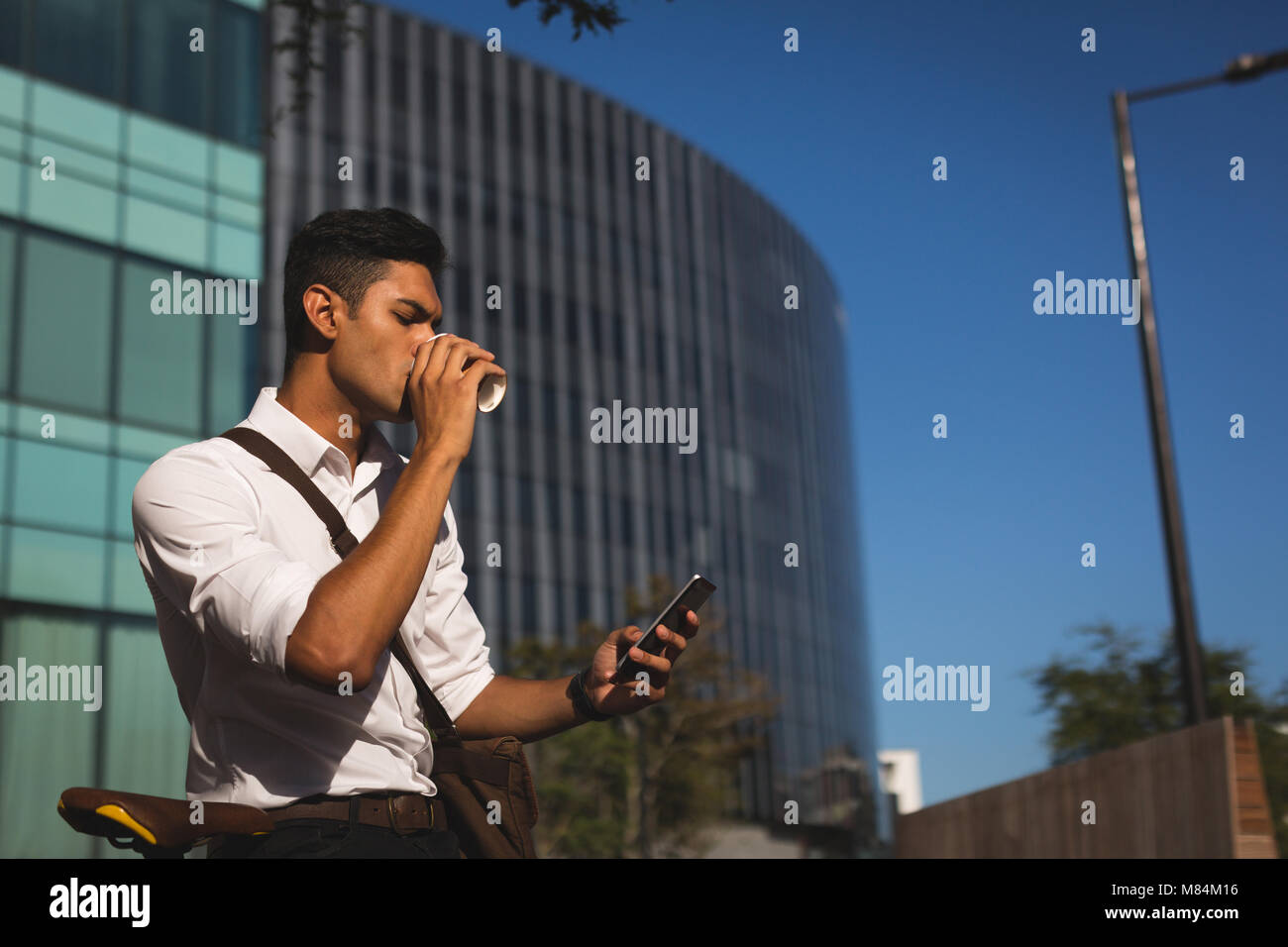 Businessman using mobile phone at office premises - Stock Image