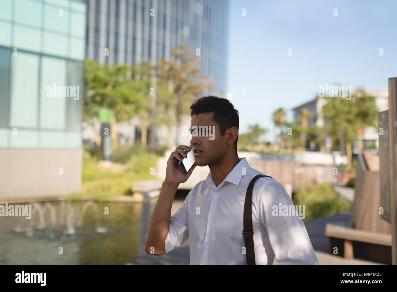 Businessman talking on mobile phone at office premises - Stock Image