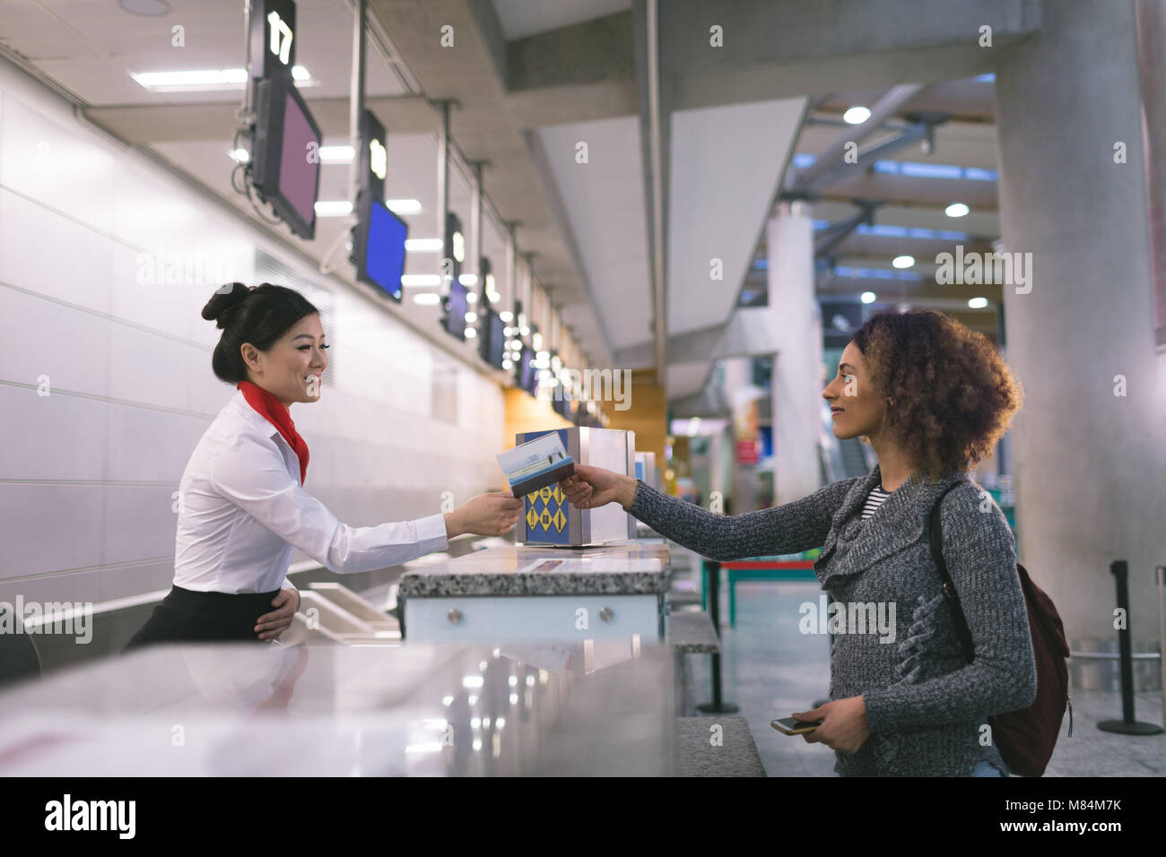 Airline check-in attendant handing passport to commuter - Stock Image