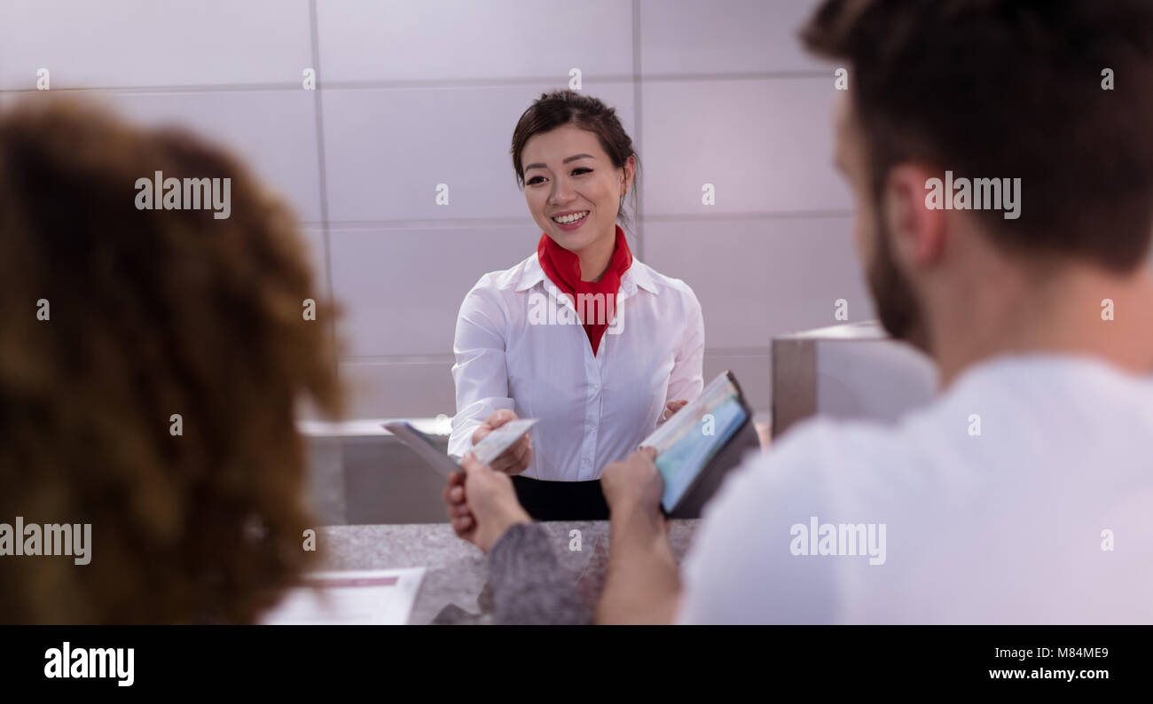 Arline attendant interacting with commuters at counter - Stock Image