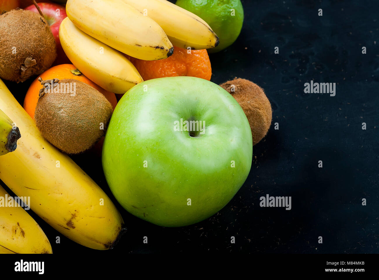 Variety of fresh fruits on dark background from slices of kiwi, bananas, aplle and orange ,copy space - Stock Image