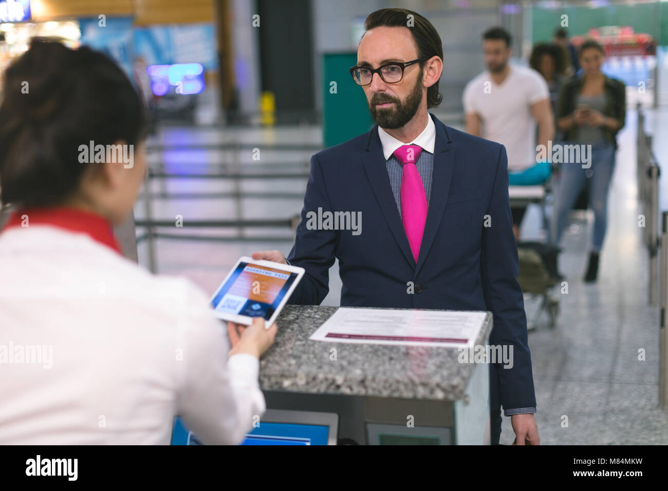 Airline check-in attendant checking ticket of commuter on digital tablet - Stock Image