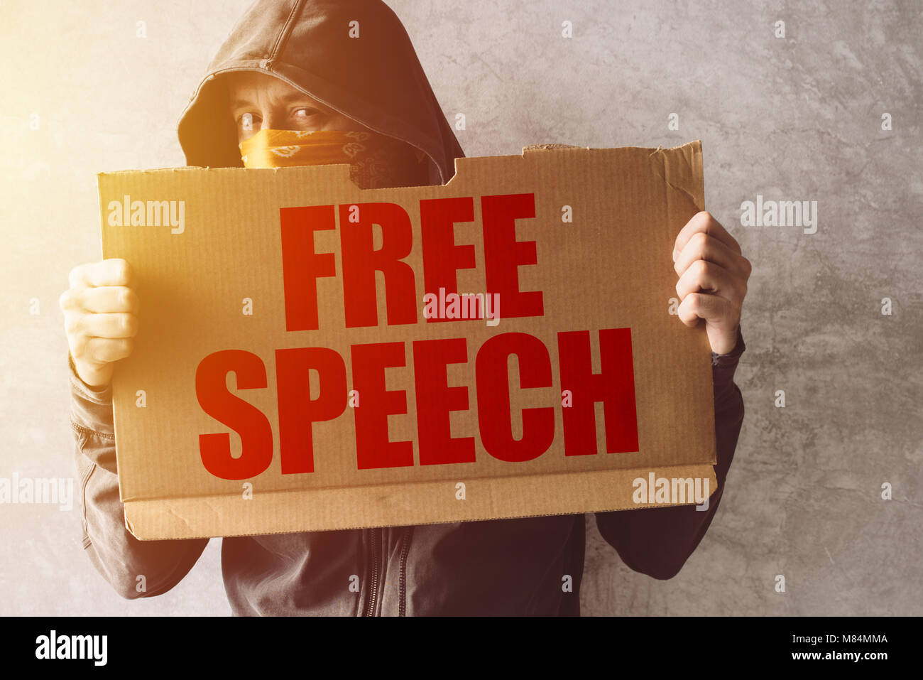 Hooded activist protestor holding Free Speech protest sign. Man with hoodie and scarf over face taking part in activism - Stock Image