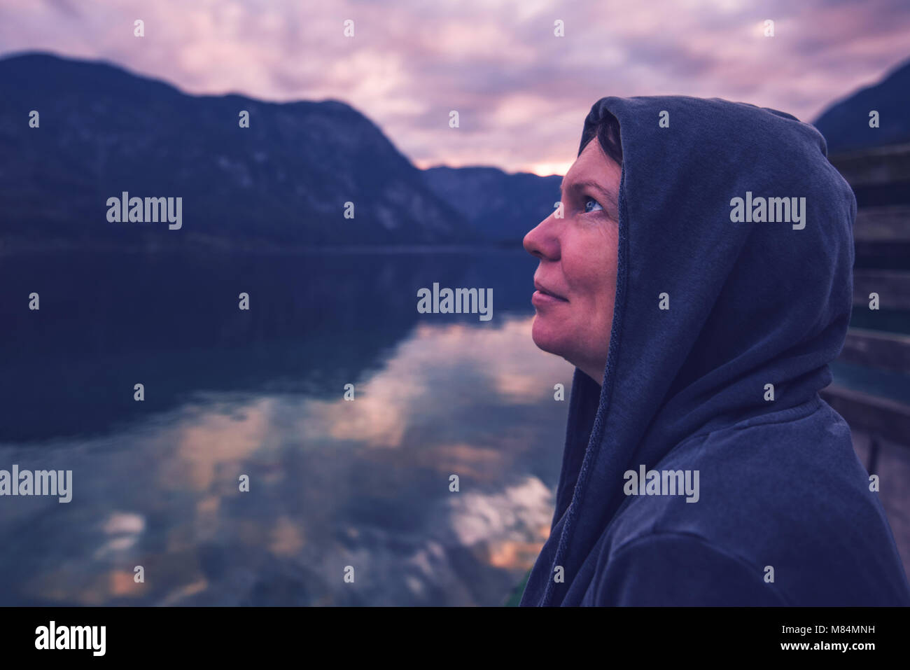 Lonely woman looking at dramatic sky. Female person in hoodie standing alone by the lake, ultra violet toned shadows - Stock Image