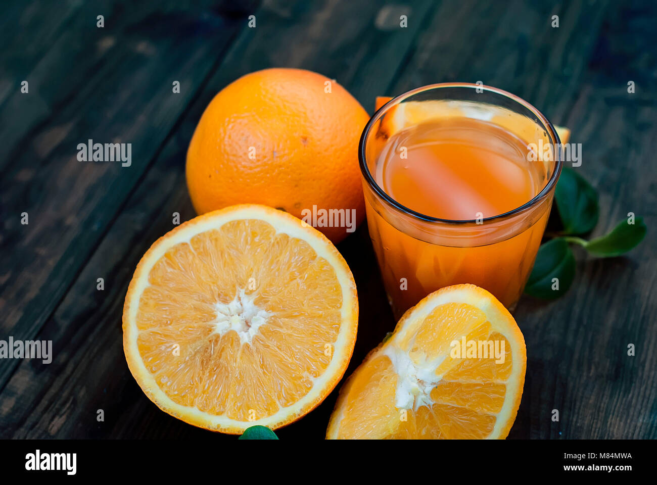 glass of fresh orange juice, whole orange and orange slices group on a dark wooden table - Stock Image
