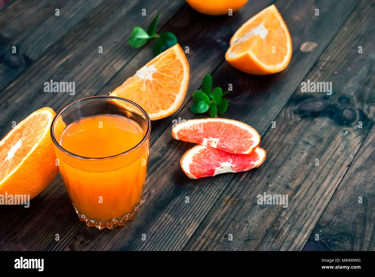 glass of fresh orange juice, whole orange and orange slices group on a dark wooden table - Stock Image