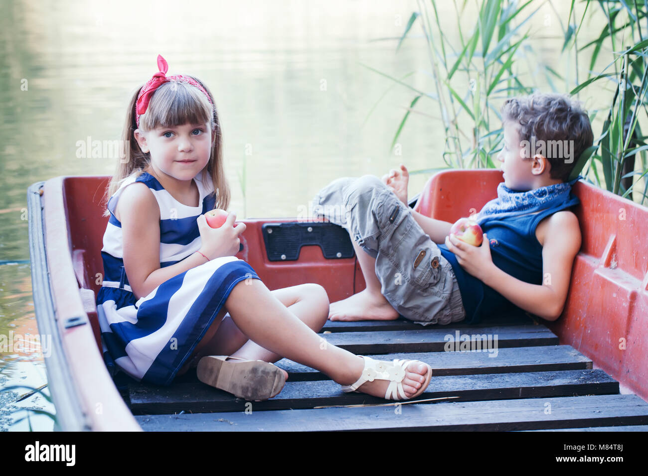 Family and friends summer vacation. Children ride on a boat outdoors. Boy with a girl riding on a boat on the lake - Stock Image
