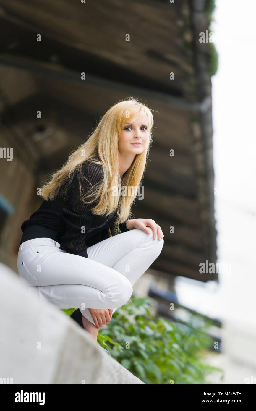One pretty teenager girl only squatting looking at camera Stock Photo