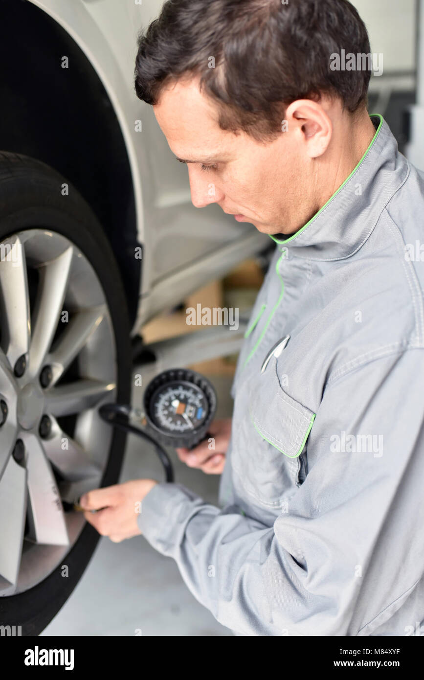 auto mechanic checks the air pressure of a tire in the garage - Stock Image
