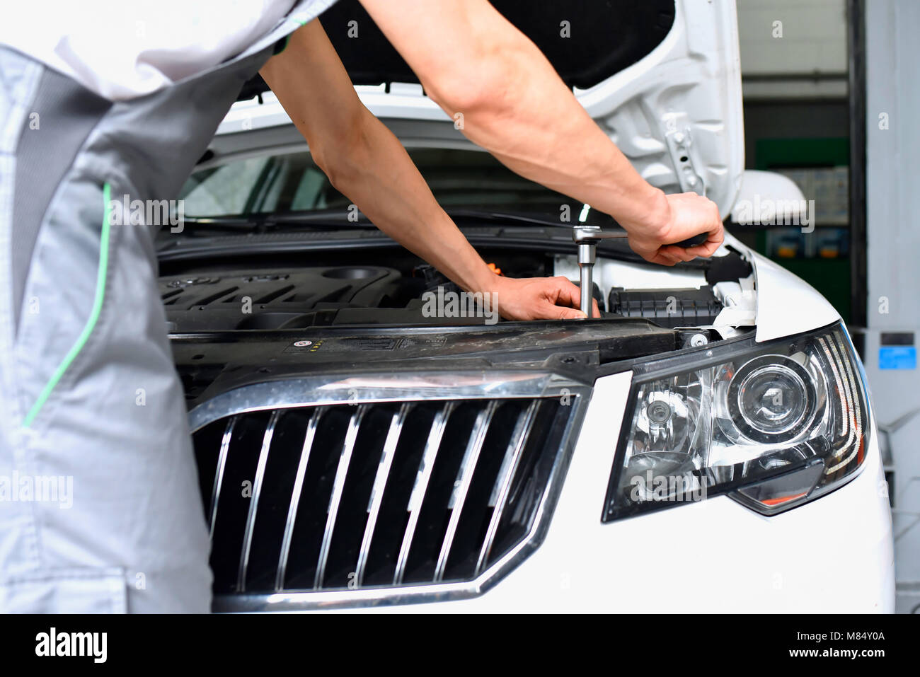 car mechanic in a workshop - closeup engine repair and diagnosis on a vehicle - Stock Image