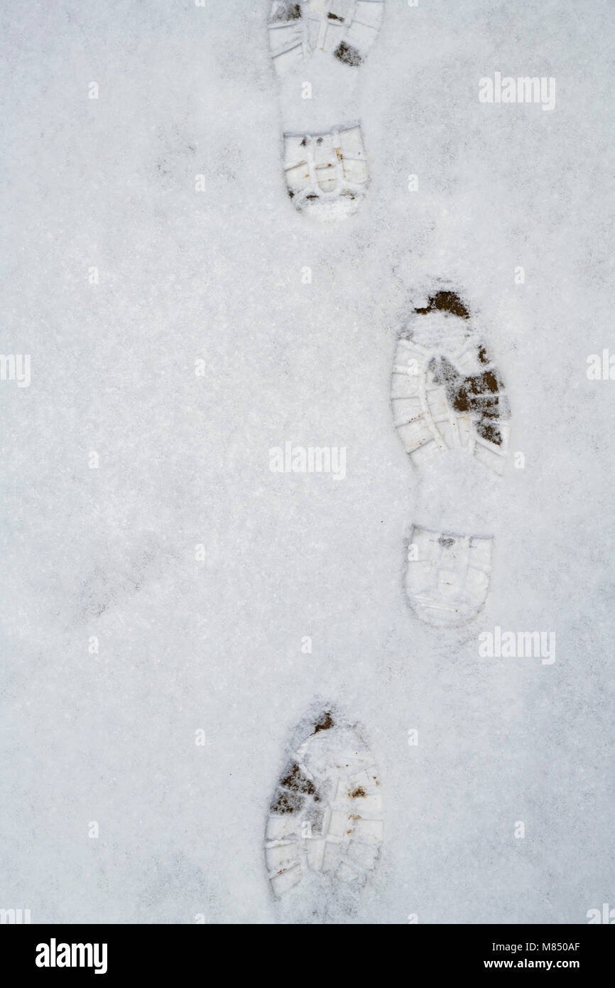Boot prints on a garden path in the snow. UK - Stock Image