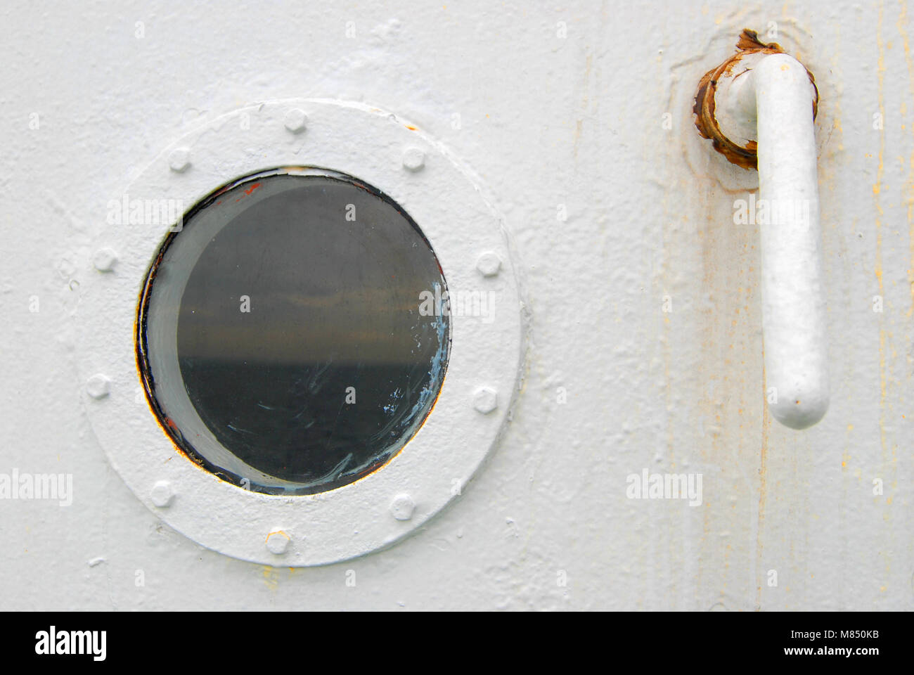 Porthole On A Ship With A Door Handle. Weathered And Rust