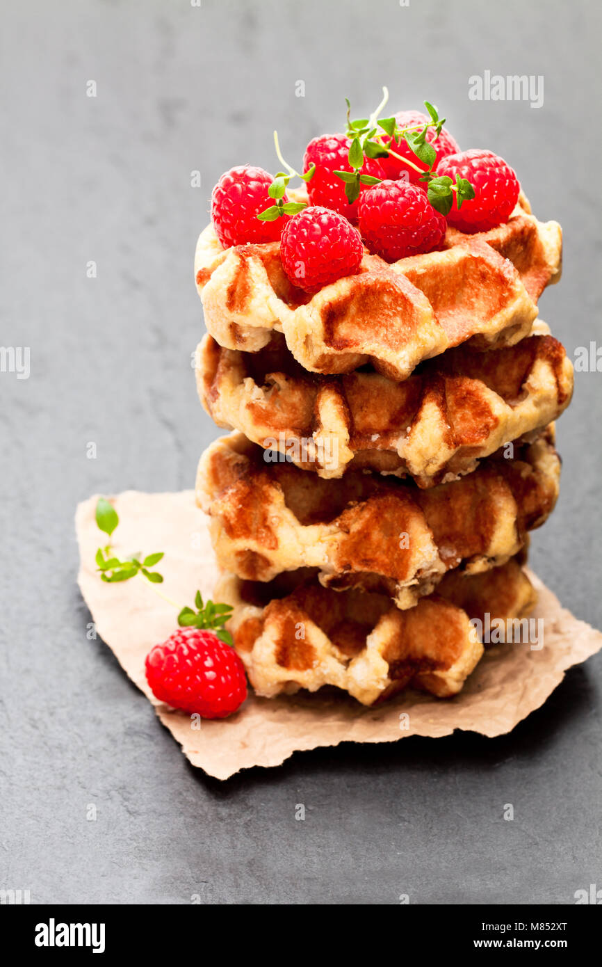 Continental  classics belgian butter waffles with raspberries on black stone background - Stock Image