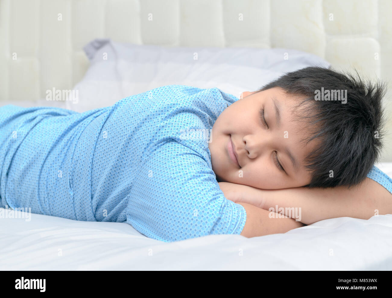 Obese fat boy sweet dream on his arm on bed healthy concept stock image