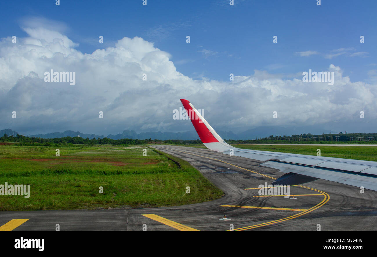 Wing of civil aircraft on runway of Chiang Mai Airport, Thailand. - Stock Image