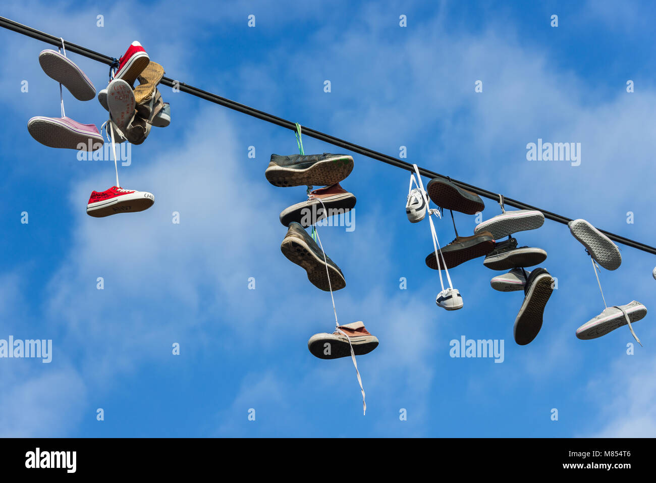 ''Shoefiti'' - pairs of shoes hanging over power wire - Stock Image