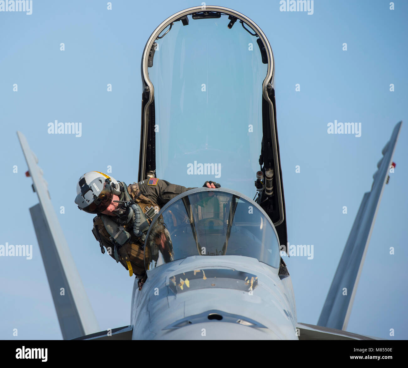 U.S. Navy Lt. Matthew Warshaw, a Strike Fighter Squadron (VFA) 115 F/A-18E Super Hornet pilot, climbs into the cockpit - Stock Image
