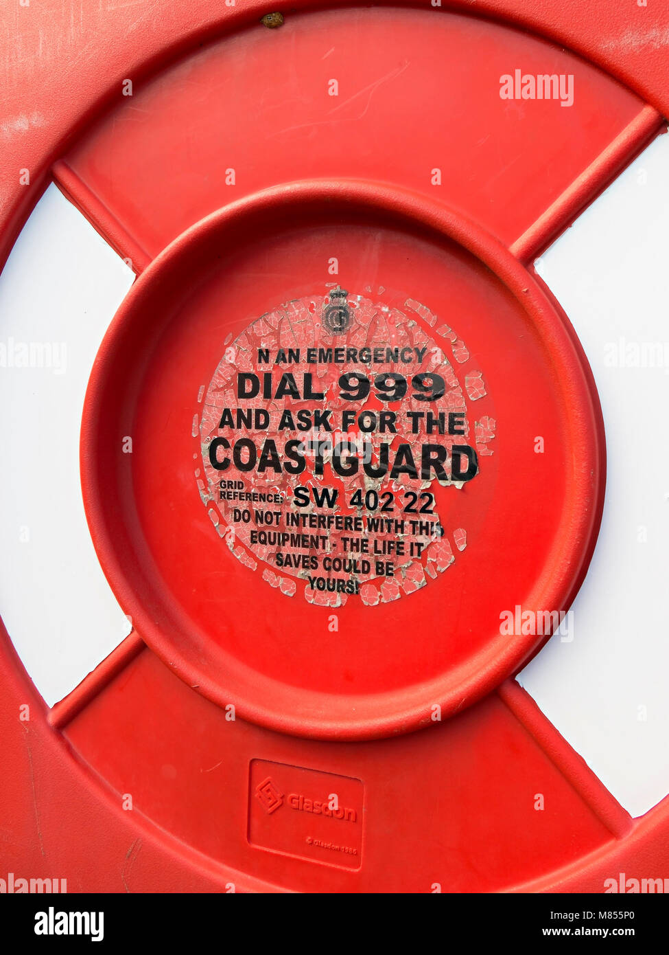 Old faded and peeling emergency services label on lifebuoy housing, Penberth Cove Harbour, Cornwall, England, UK - Stock Image