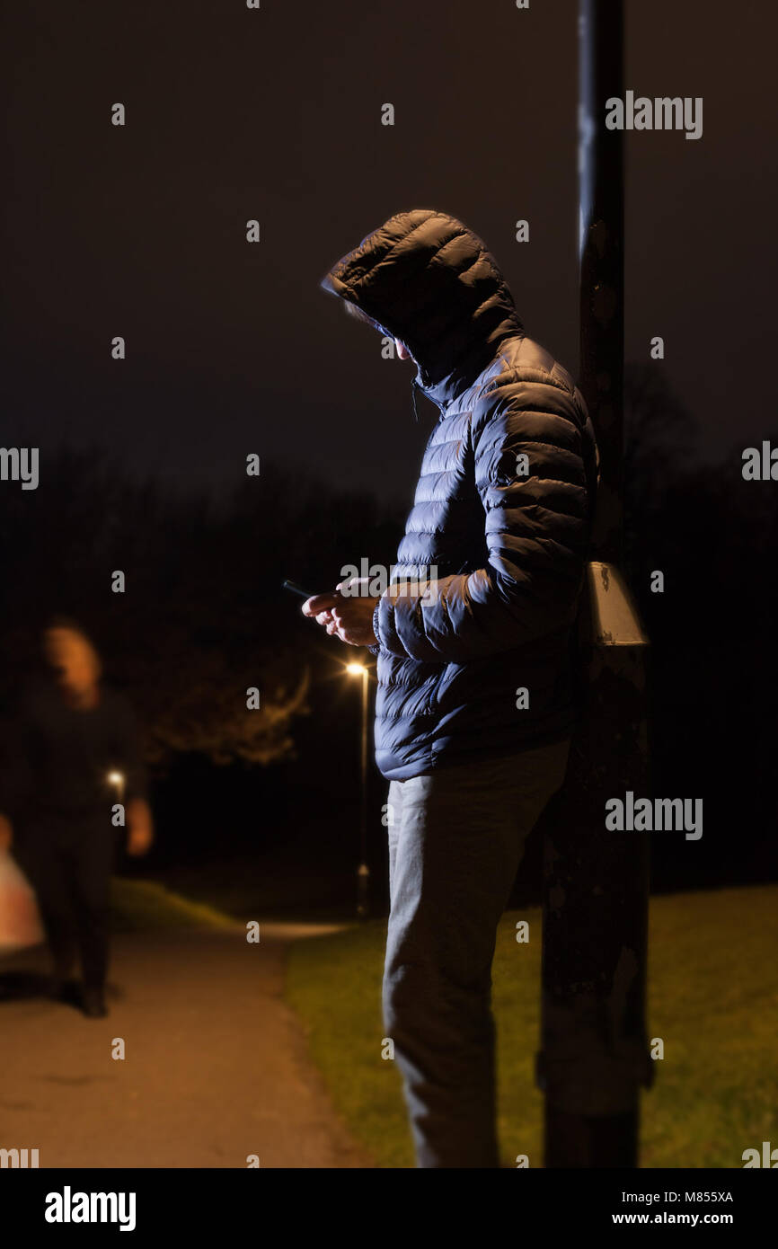 Young hooded man leaning against a lamp post in a park looking like he could be a criminal - Stock Image