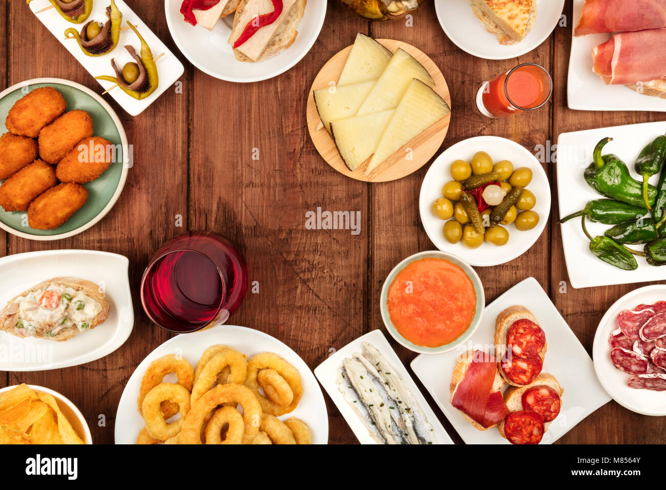 The food of Spain. An overhead photo of many different Spanish tapas, shot from above on a dark rustic texture. - Stock Image