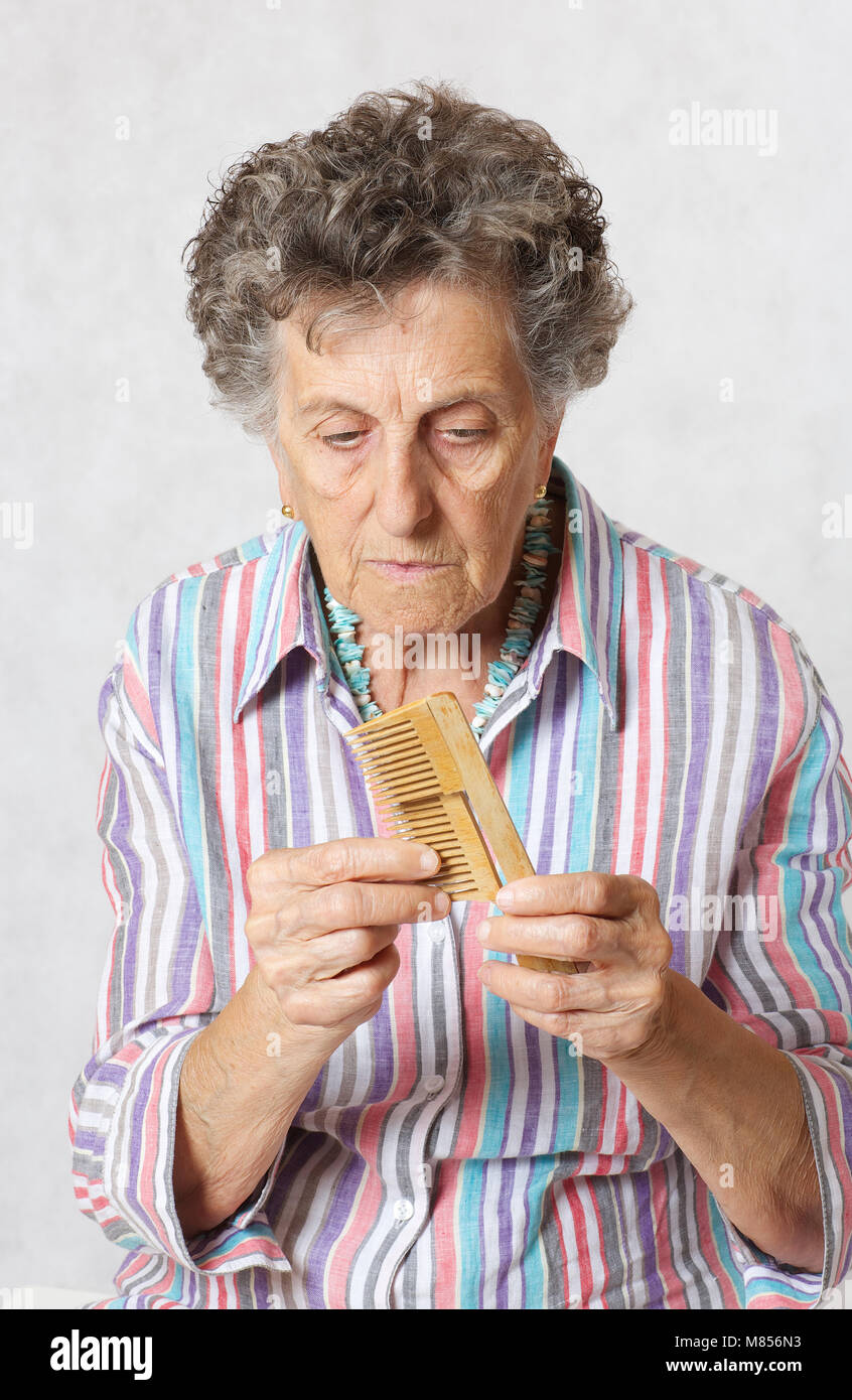 Senior woman between 70 and 80 years old with a broken woodenmade hair comb Stock Photo