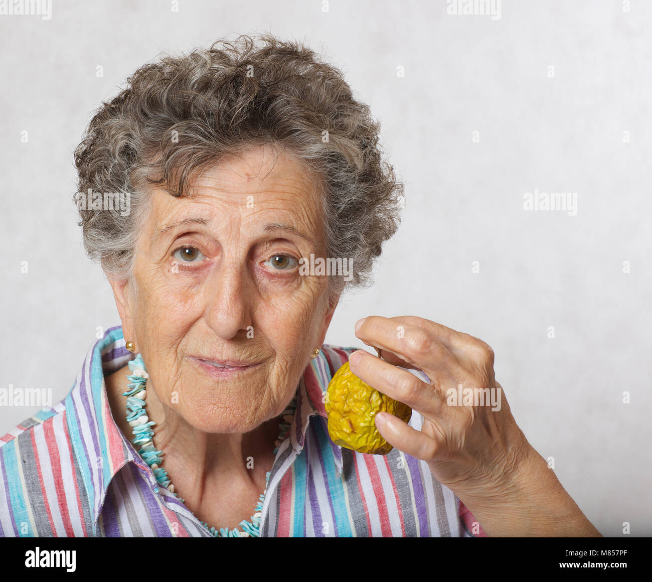 Old woman between 70 and 80 years old and shrivelled apple Stock