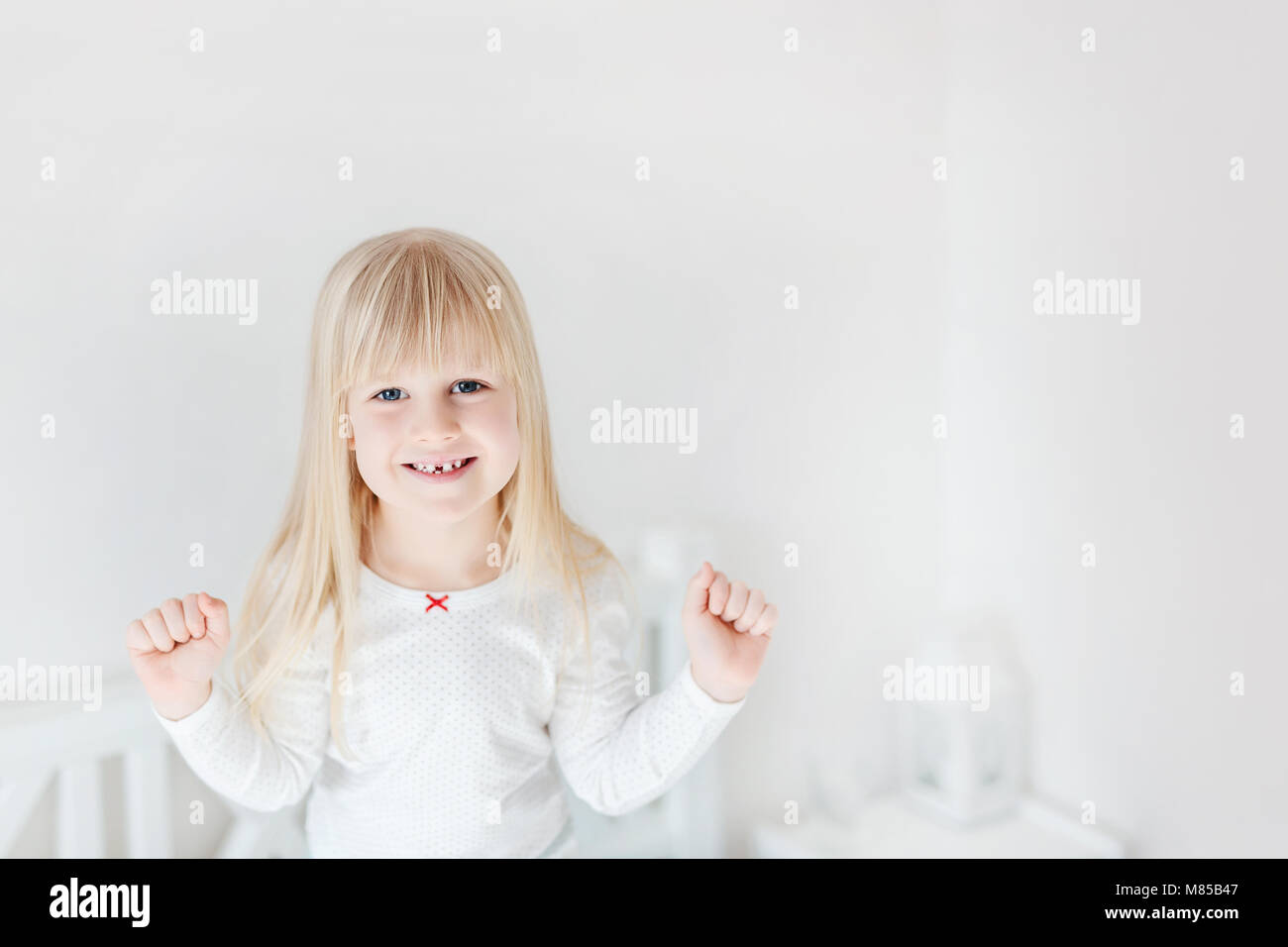 Portrait of little cute girl standing on bed. Adorable smiling child.  Blond kid raising up fists. Children victory - Stock Image