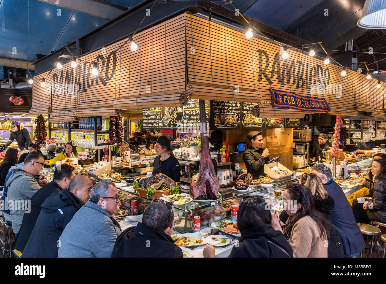 Tourists eating in a tapas bar at Boqueria market, Barcelona, Catalonia, Spain - Stock Image
