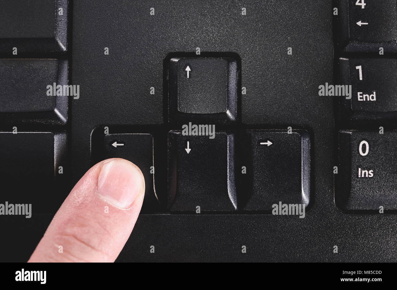 Human finger pressing the directional left key from a black keyboard. - Stock Image
