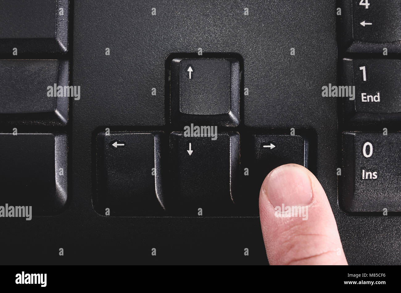 Human finger pressing the directional right key from a black keyboard. - Stock Image