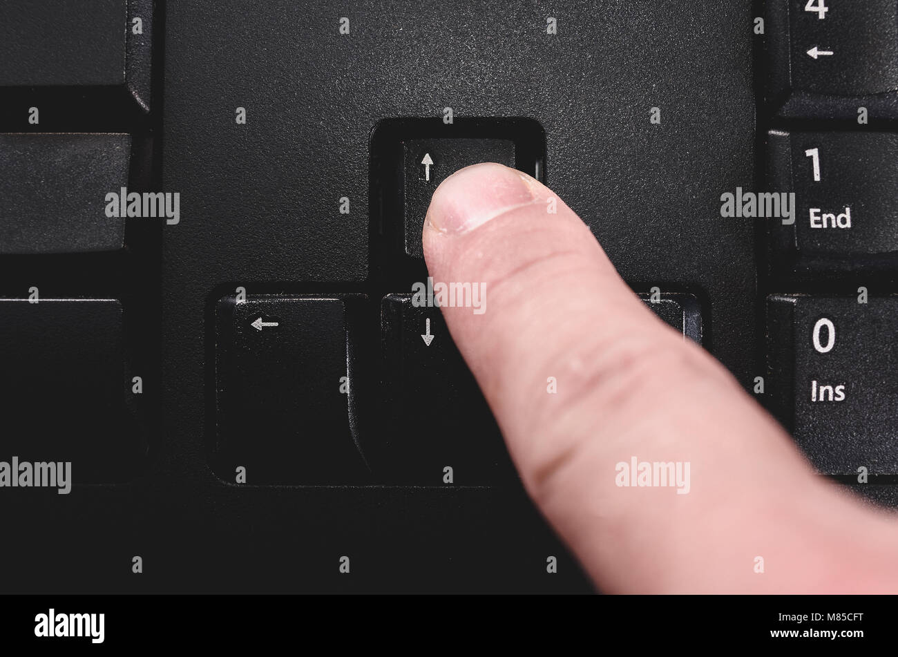 Human finger pressing the directional up key from a black keyboard. - Stock Image