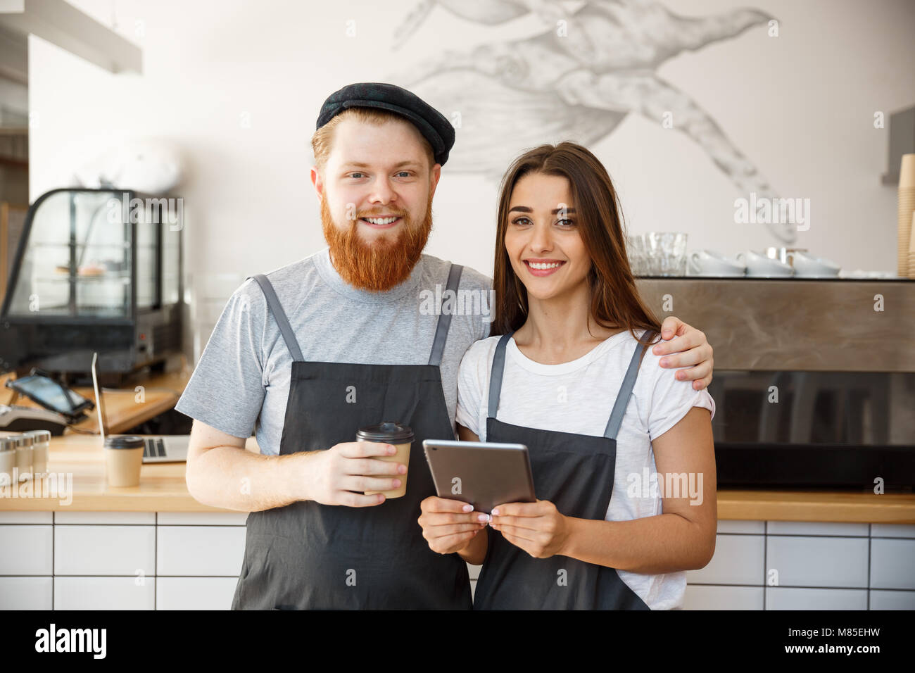 Coffee Business Concept - Portrait of small business partners standing together at their coffee shop  - Stock Image