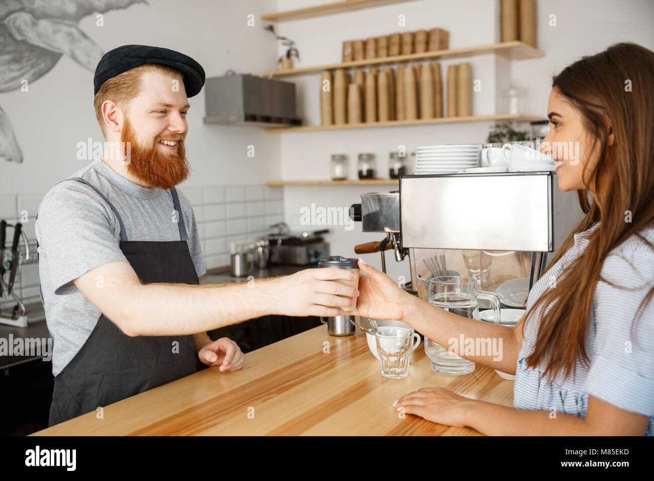 Coffee Business Concept - young beared handsome barista talking and giving take away hot coffee for beautiful caucasian - Stock Image