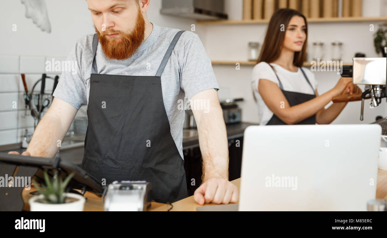 Coffee Business Concept - Young handsome bearded bartender, barista or manager posting the order from guest in digital - Stock Image