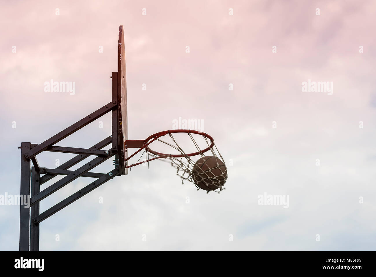 Street basketball game. Basketball shield, ball going through basket on background of sky. Concept of sport, hit - Stock Image