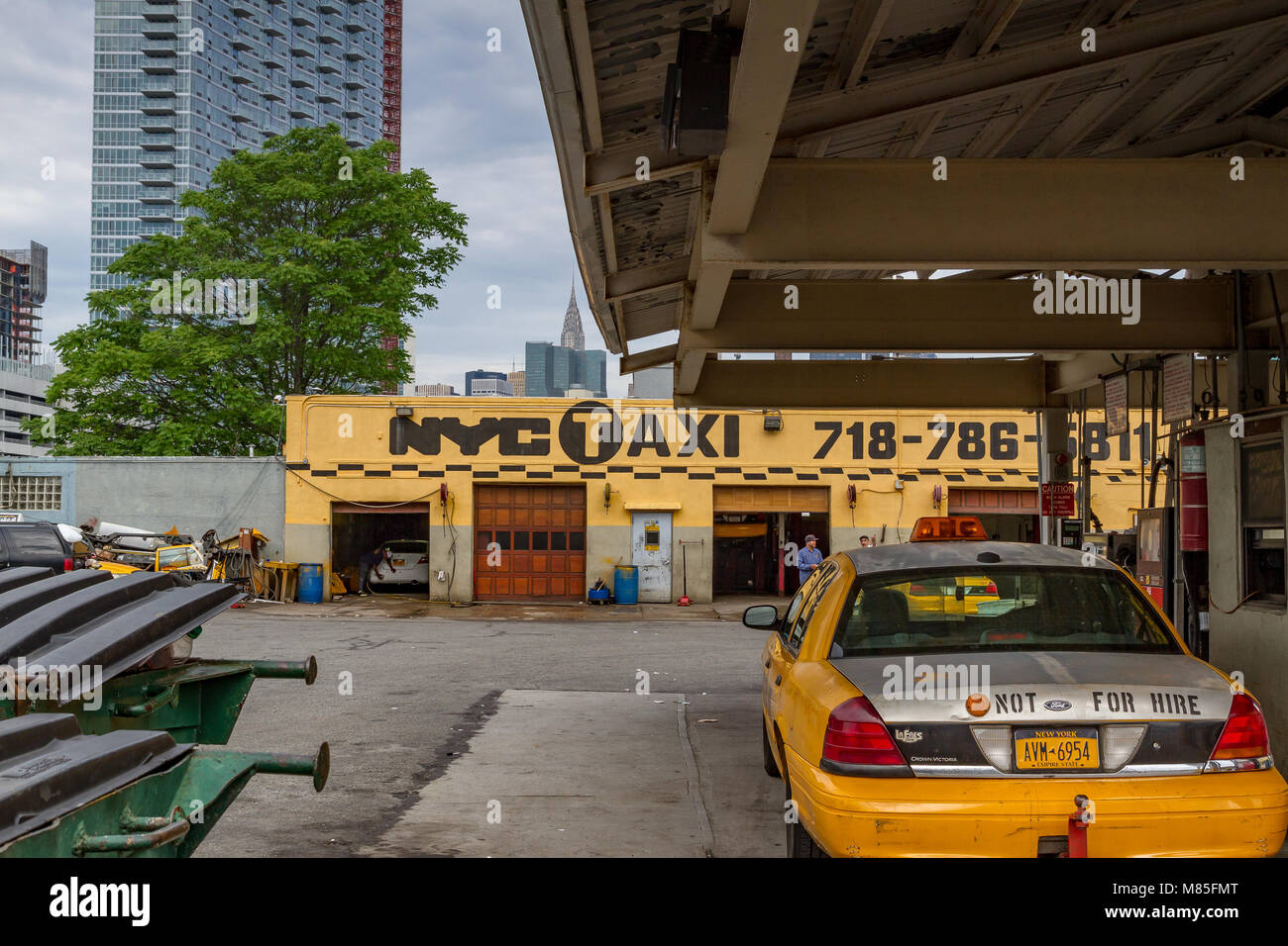 Yellow medallion taxi parked in a New York Taxi Garage,with The Chrysler Building in the Distance, Long Island City - Stock Image