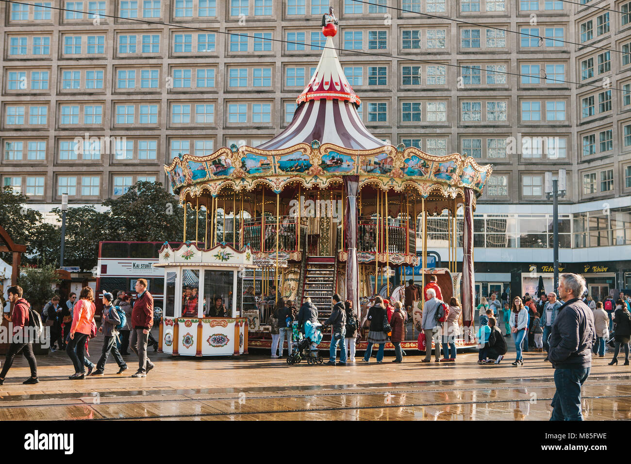 Carousel and other entertainment for people on the Alexanderplatz square. Local residents and tourists are walking - Stock Photo