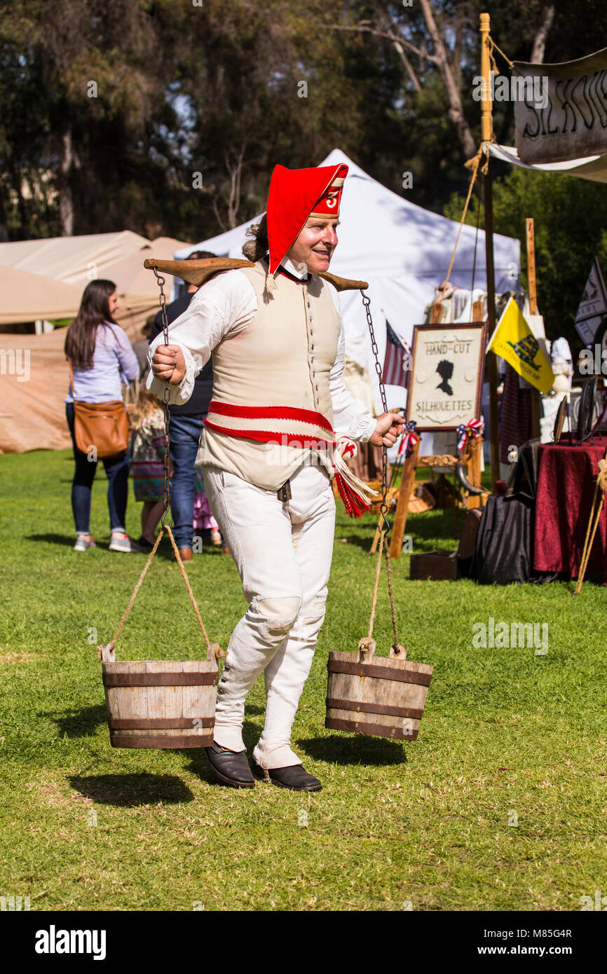A man carrying a wooden yoke on his shoulders with barrels of water hanging from it at a American Independence reenactment - Stock Image