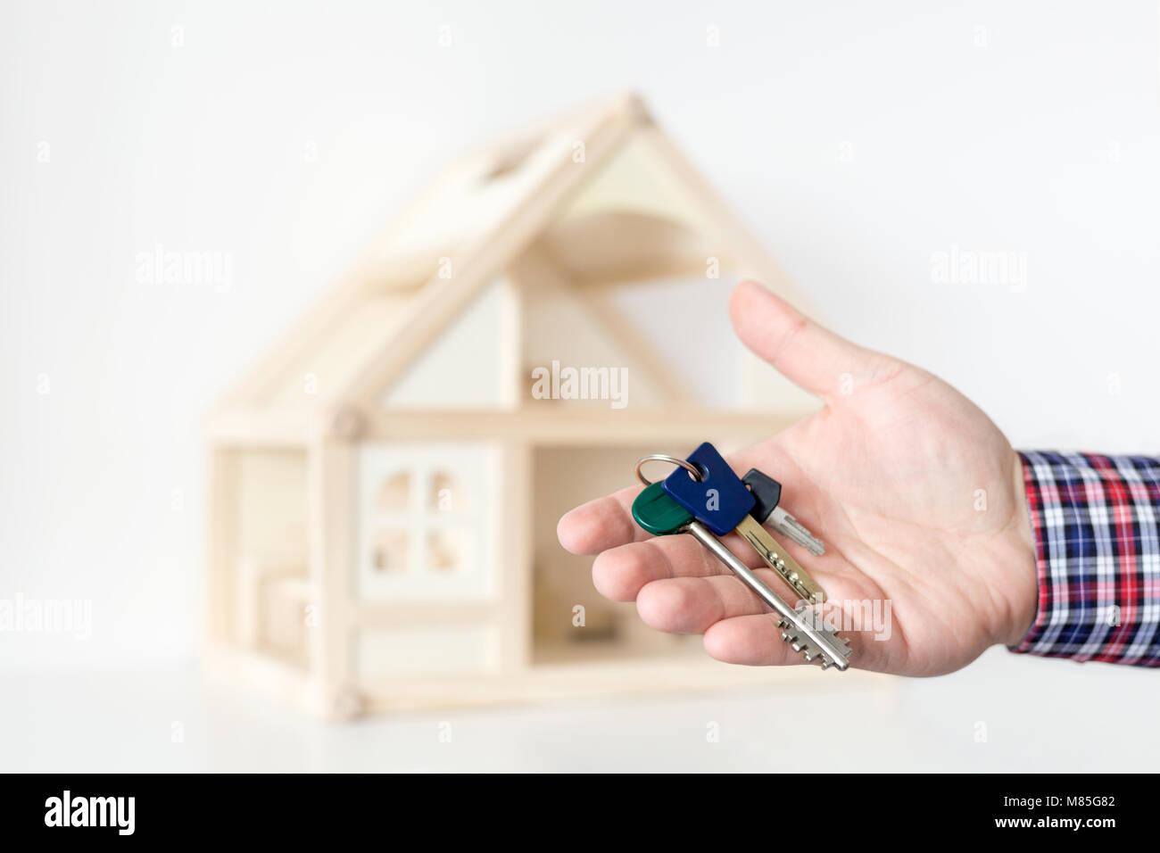 Agent's hand hold keys against house model on background.  Realtor sale offer.  Real estate investment proposition. - Stock Image