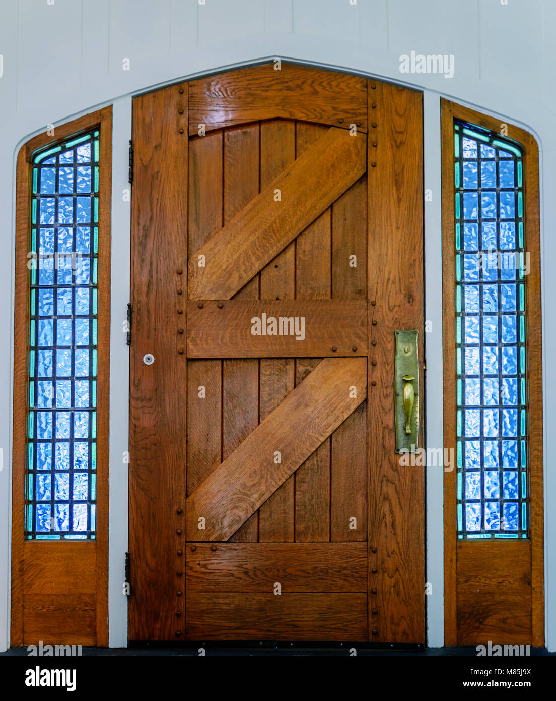 An Old Wooden Front Door Of Planks With A Metal Handle And Glass Windows  With Square