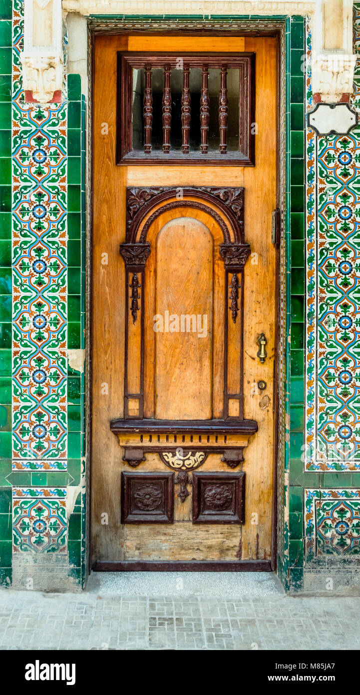 Exterior Wooden Front Door With Glass And Multi Colored Carved Ornaments,  Bronze Handle, Edging From Tile, On A City Street On A Summer Day