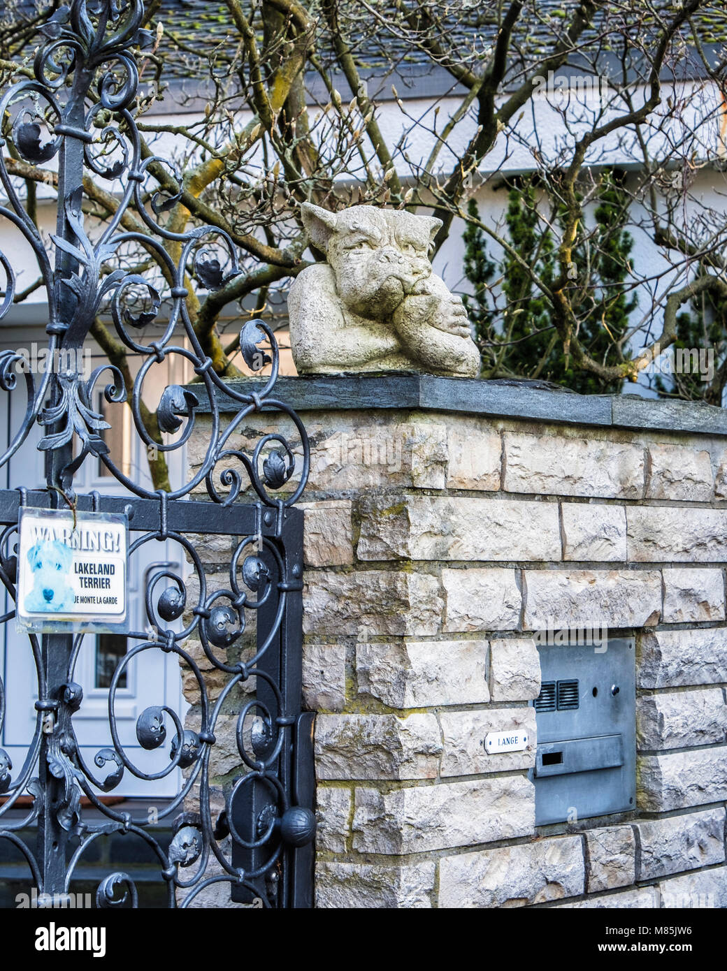 Berlin, Zehlenfdorf. Garden detail, comical grumpy dog ornament and decorative wrought iron gate - Stock Image
