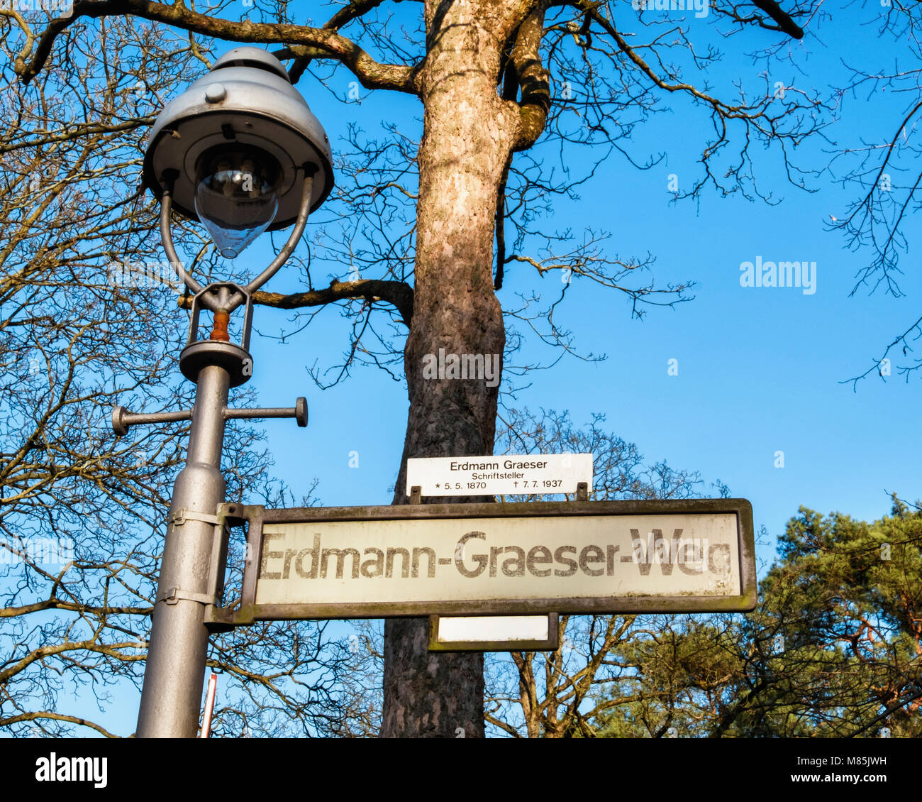 Berlin street sign, Erdmann Graeser weg. Road named after writer with historic old street lamp and blue sky - Stock Image