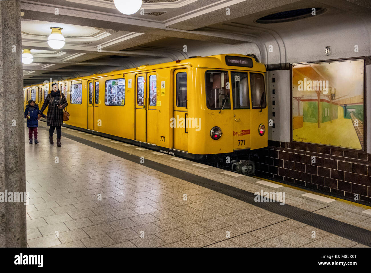 Berlin Dahlem District,Breitenbachplatz U-Bahn underground railway station interior, yellow train and woman with - Stock Image