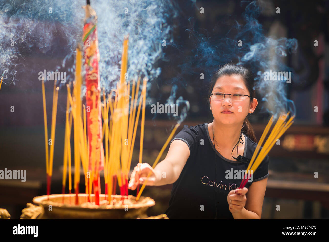 Woman prayer Southeast Asia, a young woman worships in the Thien Hua pagoda - temple - in the Cholon area of Ho - Stock Image